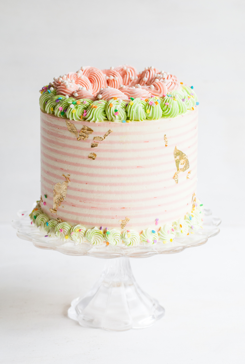 Rhubarb Crisp Unicorn Cake with striped buttercream, gold leaf and sprinkles.