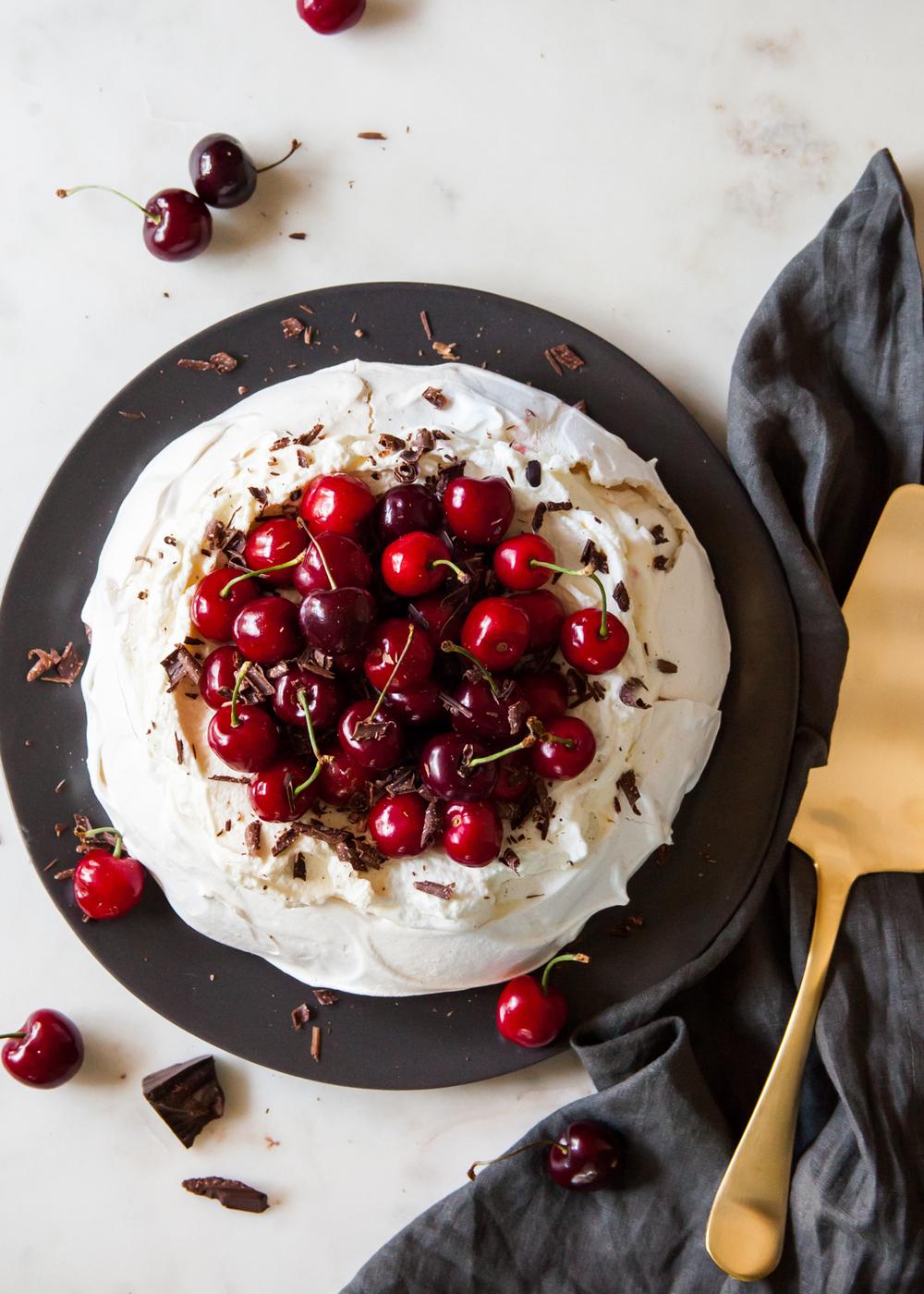 Pavlova with almond cream, fresh cherries, and chocolate shavings.