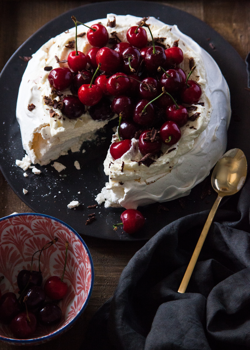 Pavlova with almond cream, fresh cherries, and chocolate shavings.