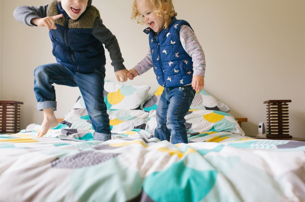Two children jumping on the bed during a Maitland Photography session.