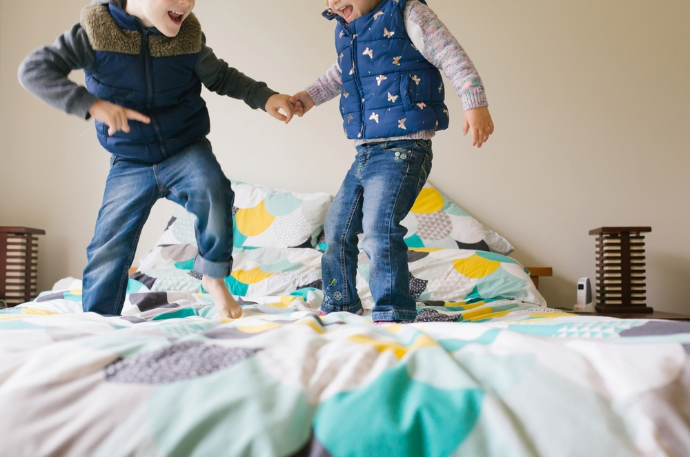 Children jumping on the bed during an at home family photography session in Maitland