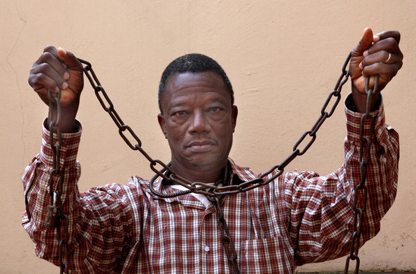 Gregory Ahongbonon, founder of Saint Camille de Lellis Association, hold chains used to restrain a person with mental illness.