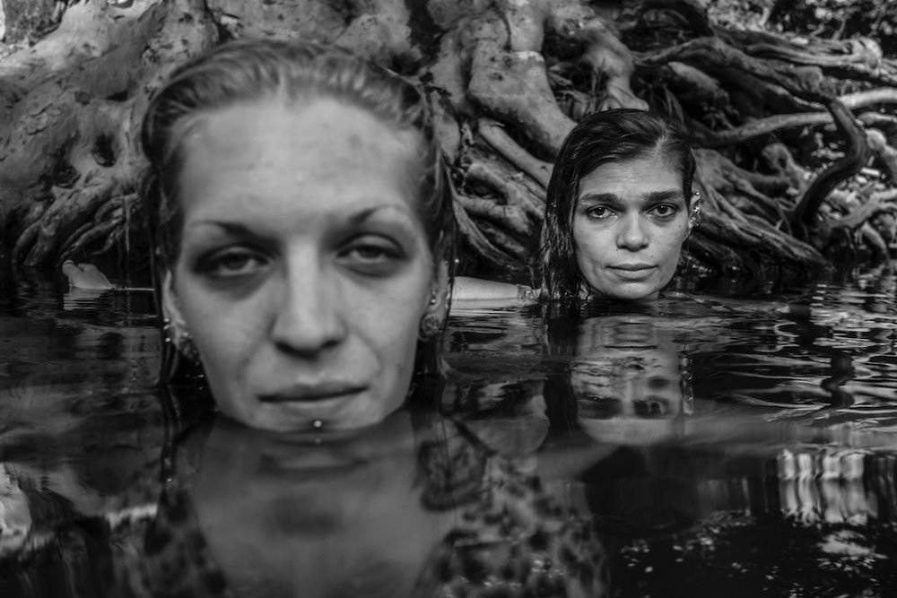 """This photograph was taken at a watering hole near a drive-in movie theater on the outskirts of town. Their names are Emily and Belinda. I spoke to them for hours about their lives. They said they hadn't been swimming for years because they'd both been in terrible car accidents that limited their mobility."" ©Caleb Stein, July 2018."