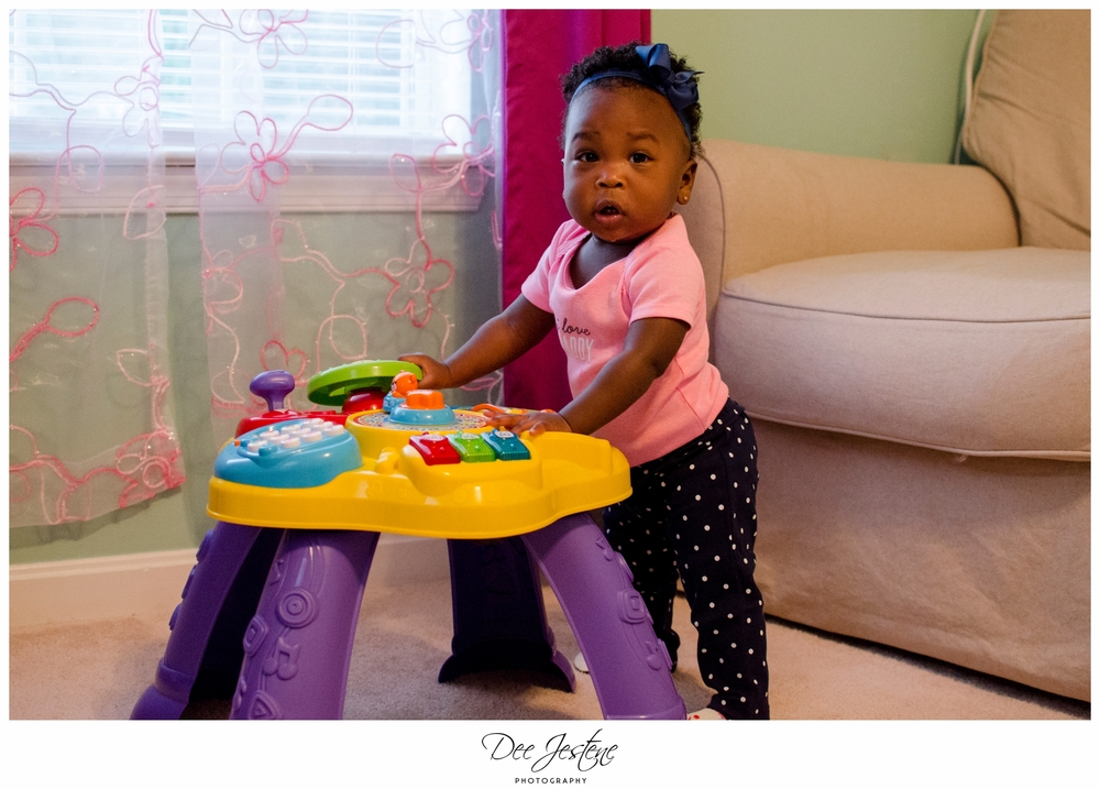 Baby Girl Standing next to toy