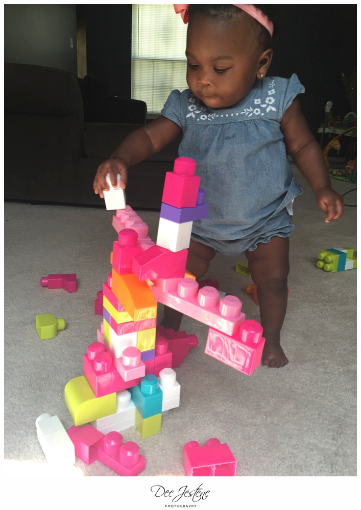 african american baby toddler girl standing playing with blocks