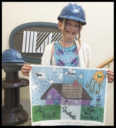 Jozey Donze proudly holding her winning artwork.