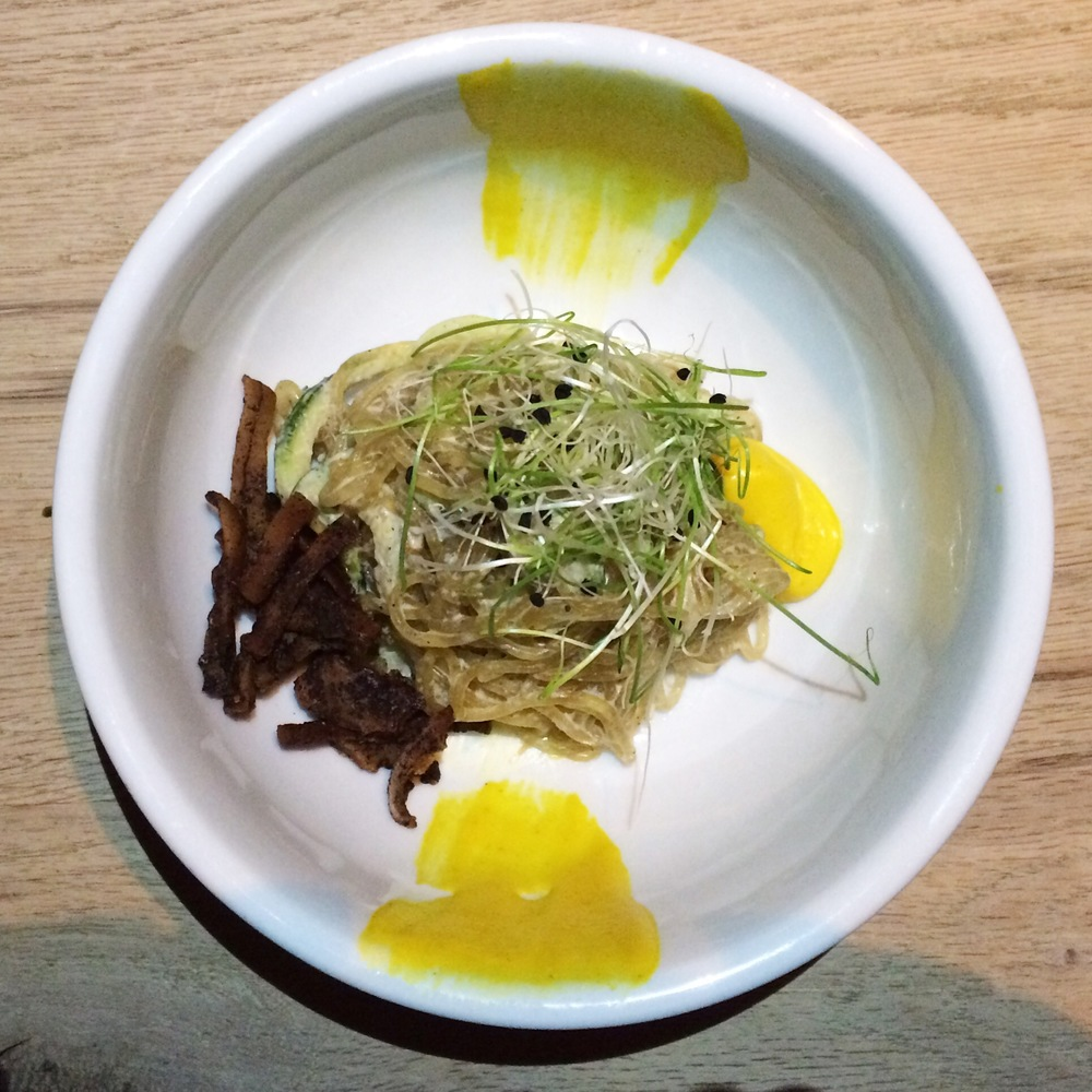 Sixth Course Spaghetti Alla Carbonara kelp and zucchini noodles, black pepper cream, smoked coconut bacon, peas, asparagus, mint, coconut yolk, black olive oil.