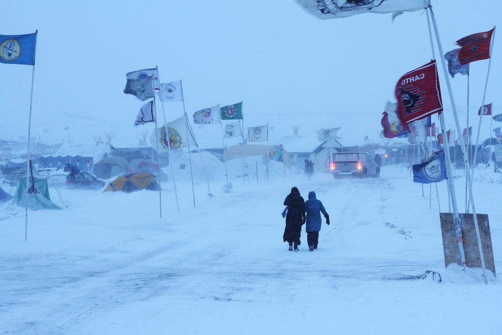 "Two women walk down ""Flag Alley,"" the main road in Oceti Sakowin Camp, during the first blizzard of the winter."