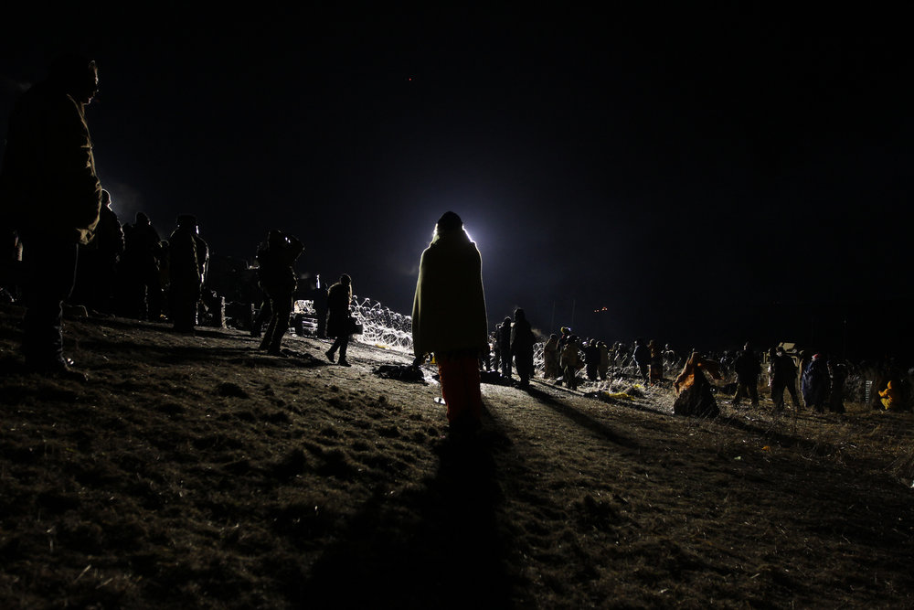 "A woman wraps herself in a blanket and faces the spotlights of the police barricade during an all night stand-off at the ""Backwater Bridge"" on ND 1806, one quarter mile north of Oceti Sakowin Camp."