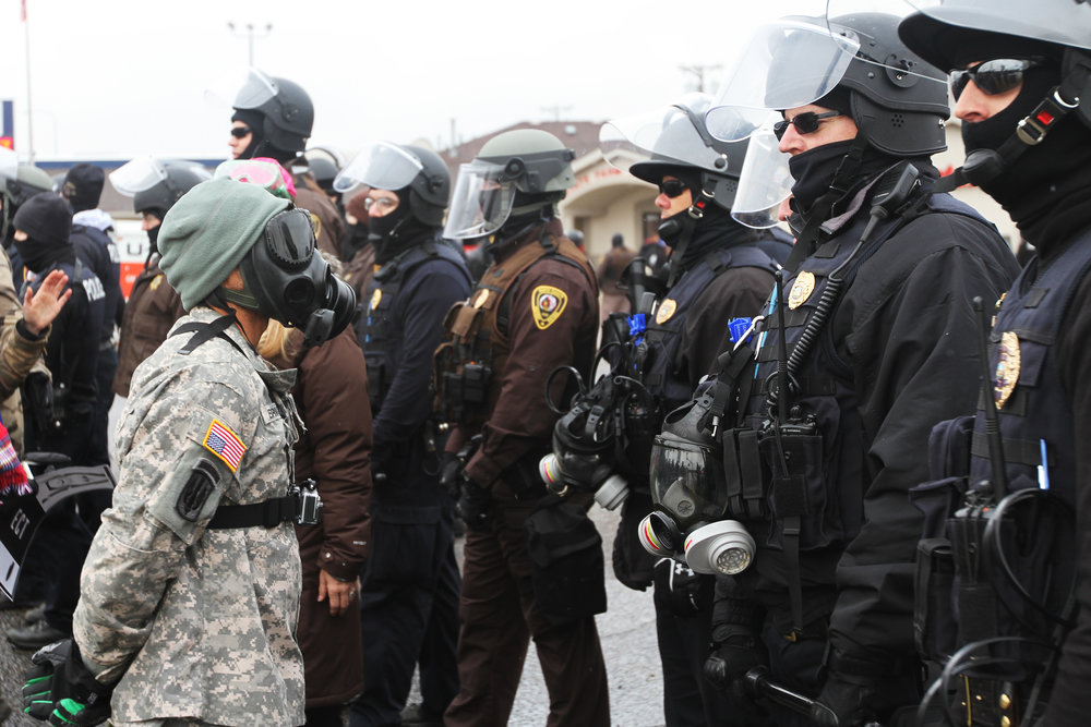 A water protector faces police in Mandan, ND on Thanksgiving Day.