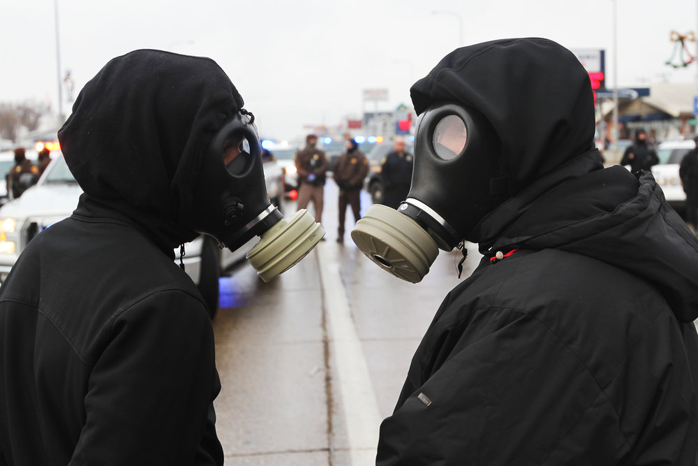 Two protestors confer in front of a line of police in Mandan, ND on Thanksgiving Day.