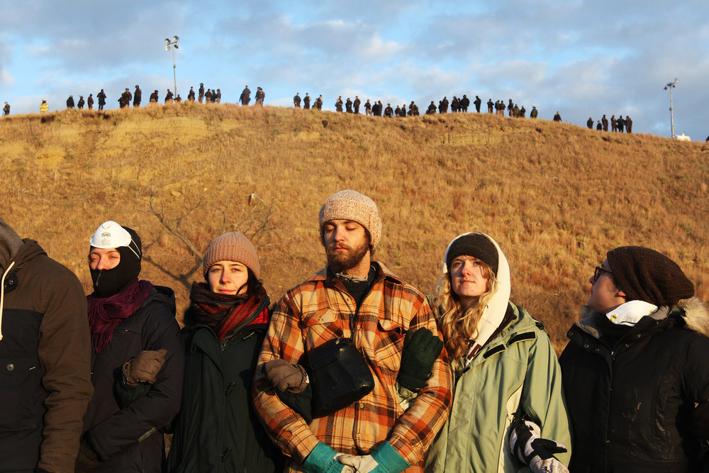 Protestors stand in prayer circle while police stand watch on top of Turtle Island, an ancient burial ground. The next morning, police placed barbed wire around the island and smashed holes into the canoes and kayaks.