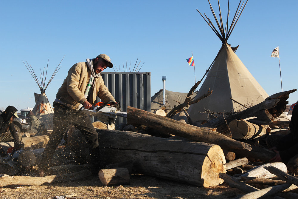 A supporter cuts wood in preparation for a harsh winter on the plains.