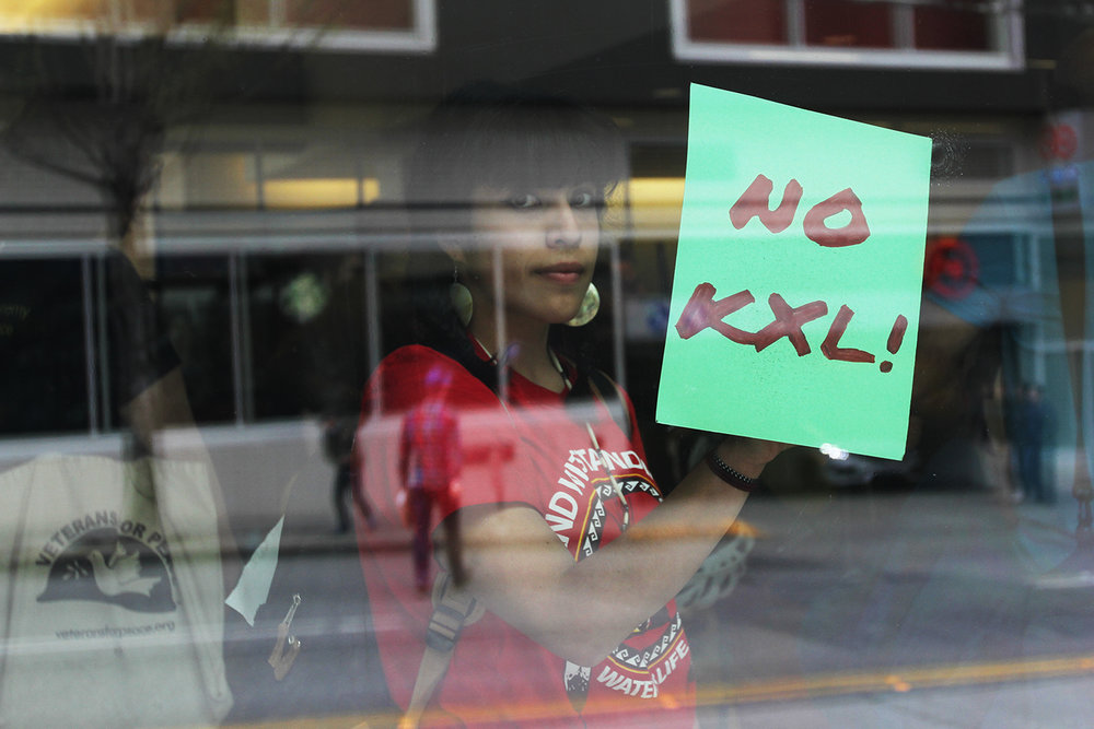 "A protestor holds a sign reading ""No KXL"" inside of a Chase bank location in Seattle, WA to speak against the bank's funding of the Keystone XL Pipeline."
