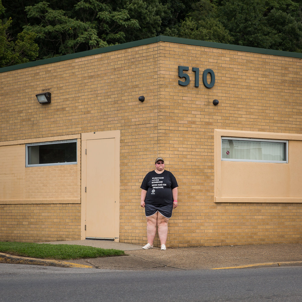 Here, Rachel stands outside the only abortion clinic in the state of West Virginia. This is where she had her second abortion performed. It's an unassuming building on an unassuming street — a stark contrast to the heated discussions surrounding the topic, as well as the violence perpetrated against people who need or perform abortions. Extracted from the heated debate, Rachel is just a person, and the abortion clinic is just a building where medical procedures take place.