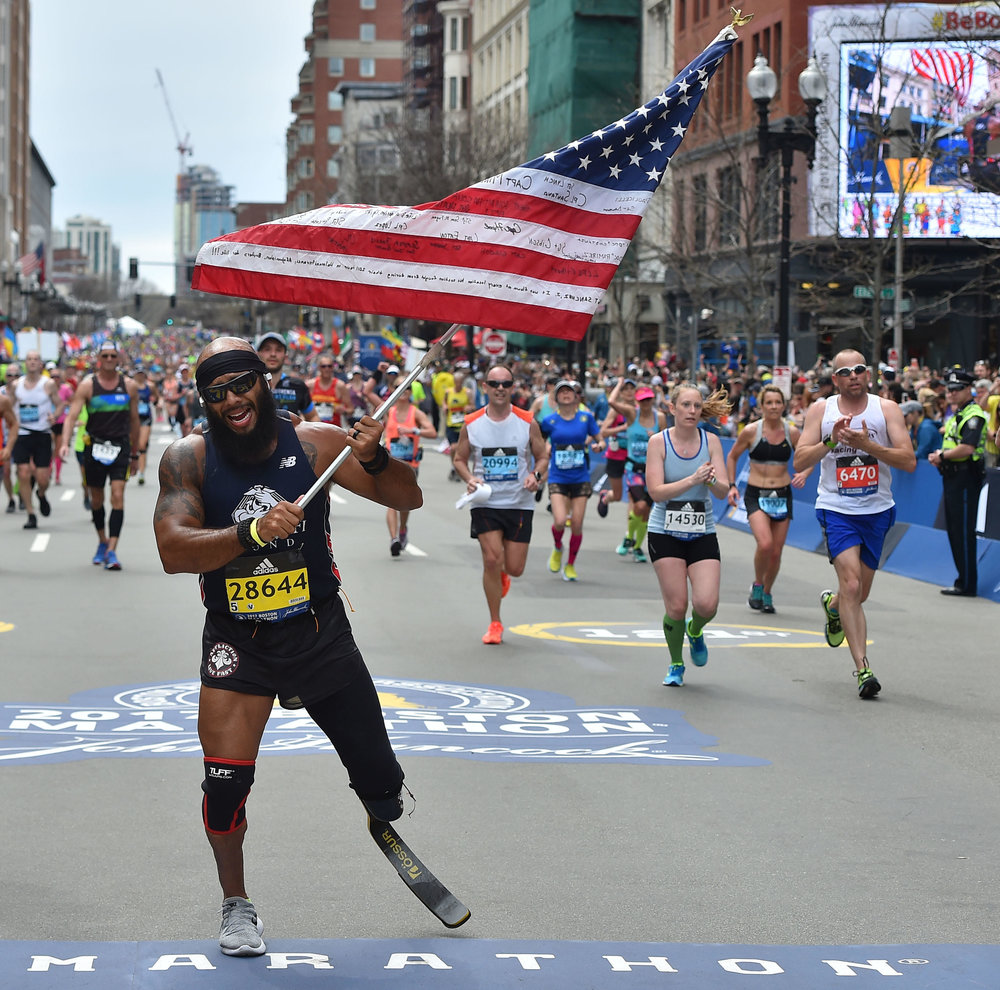 An amputee Marine running with the American flag held high. Boston Marathon 2017.
