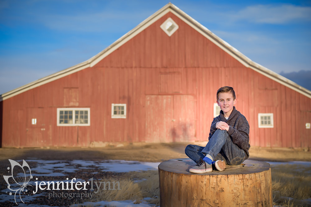 Son Sitting on Stump By Red Barn