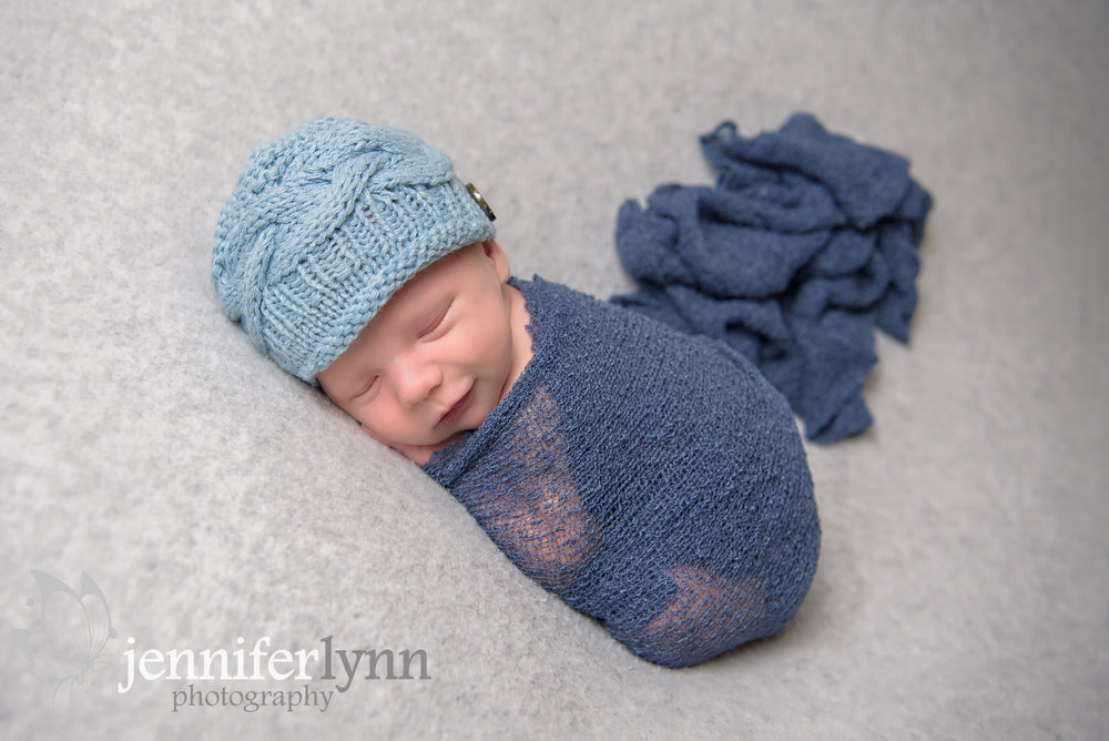 Newborn Boy Grey Blanket Blue Hat Smirk