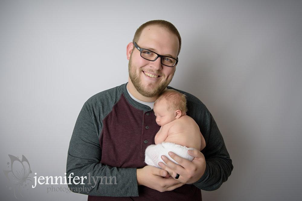 Newborn Boy Curld up on Dad's Chest