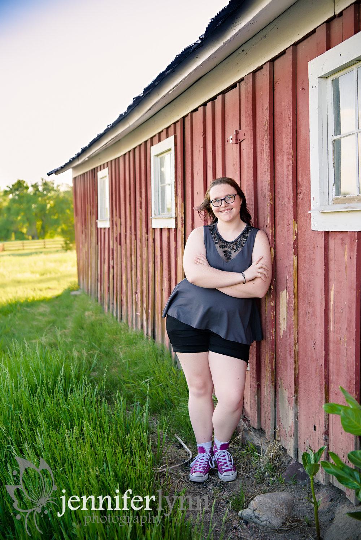 Senior Girl Leaning Red Barn