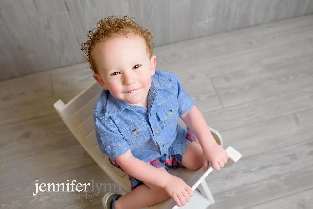 Toddler Boy Sitting on White Bench