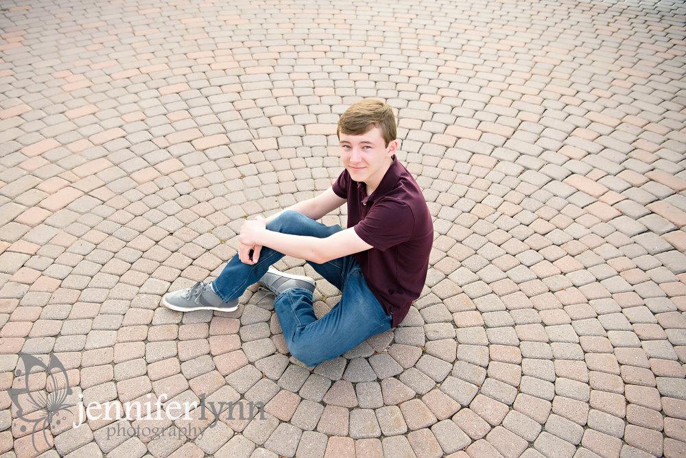 Senior Boy sits on spiral brick patter on ground