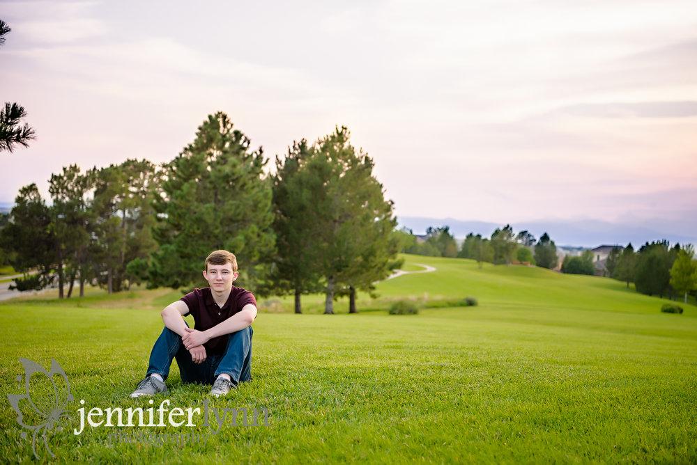 Senior Boy Sitting on Green Hill Mountains Sunset