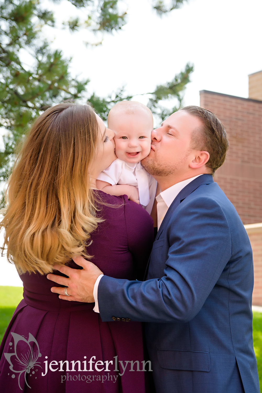 Family of Three kissing baby