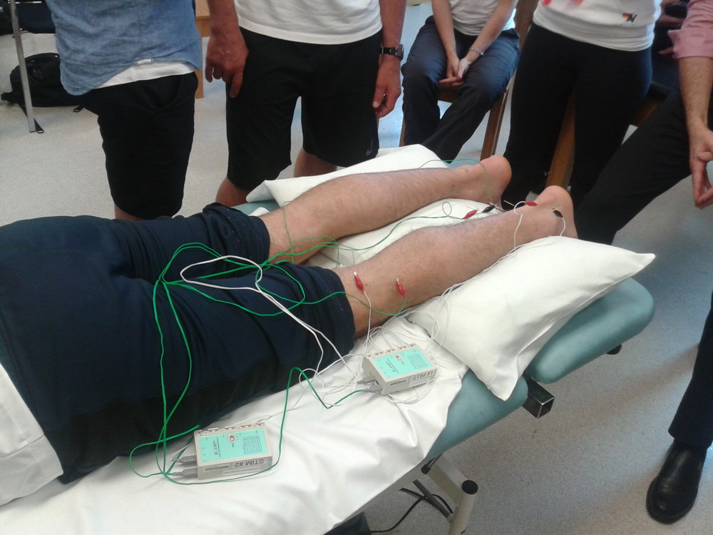 A demonstration of electro-acupuncture for a lower body injury