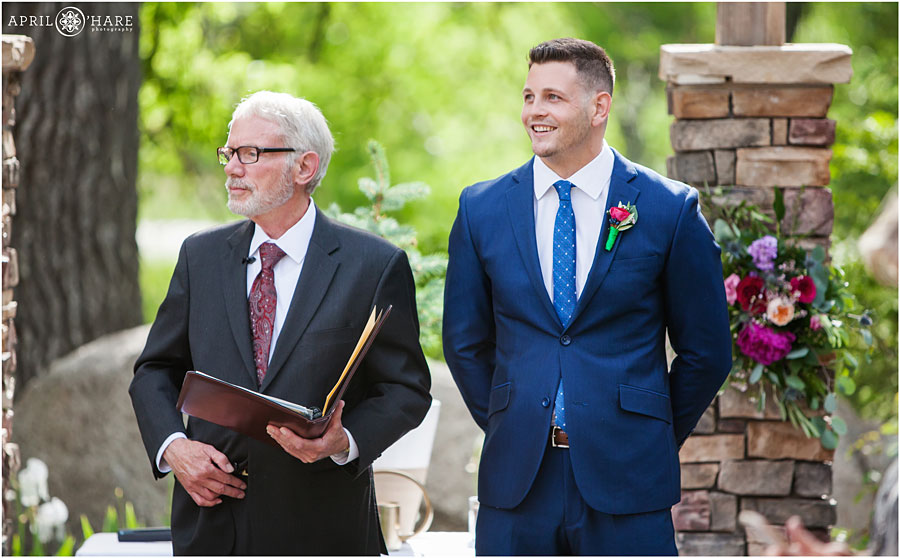 Groom-Smiles-when-he-sees-his-bride-for-the-first-time-on-their-wedding-day-at-Wedgewood-on-Boulder-Creek-in-Colorado.jpg