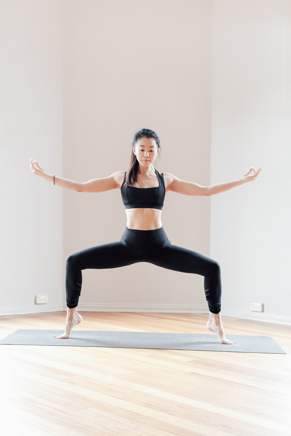 Jowing Zhang in a Yoga Balancing Pose Goddess Pose at Little Mandarin