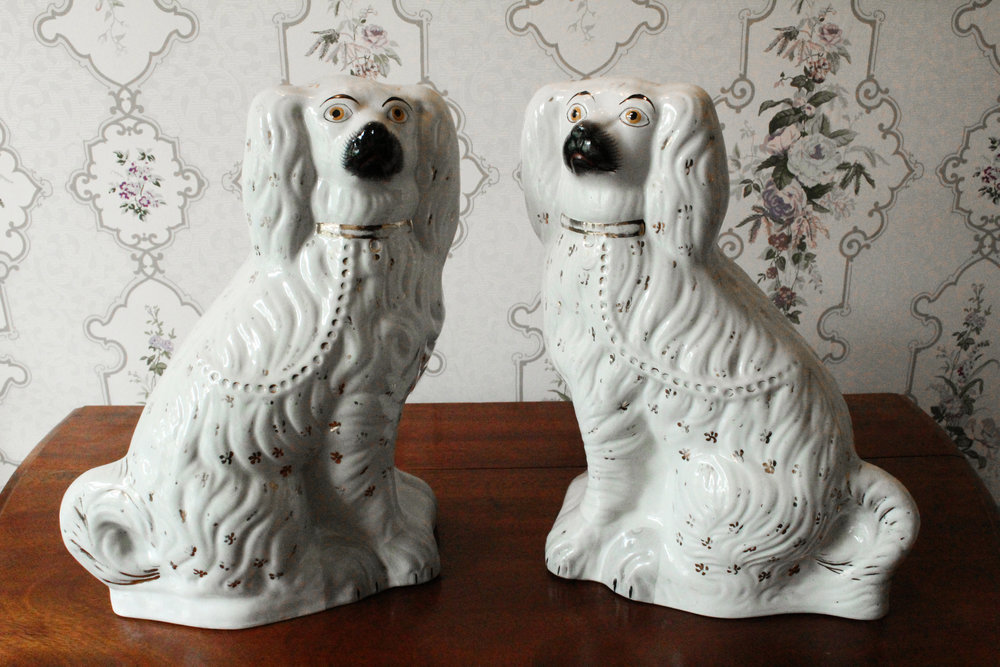 Ceramic Staffordshire Dogs    Medium adoptable, $100 donation   Two white ground ceramic dogs that live in Daisy's room. They have gray shading accenting their paws. Both dogs are embellished with gilt—a thin covering of gold leaf or gold paint. The gilt flowers and other gilt markings appear on the dogs' collars, leashes, and throughout their fur.