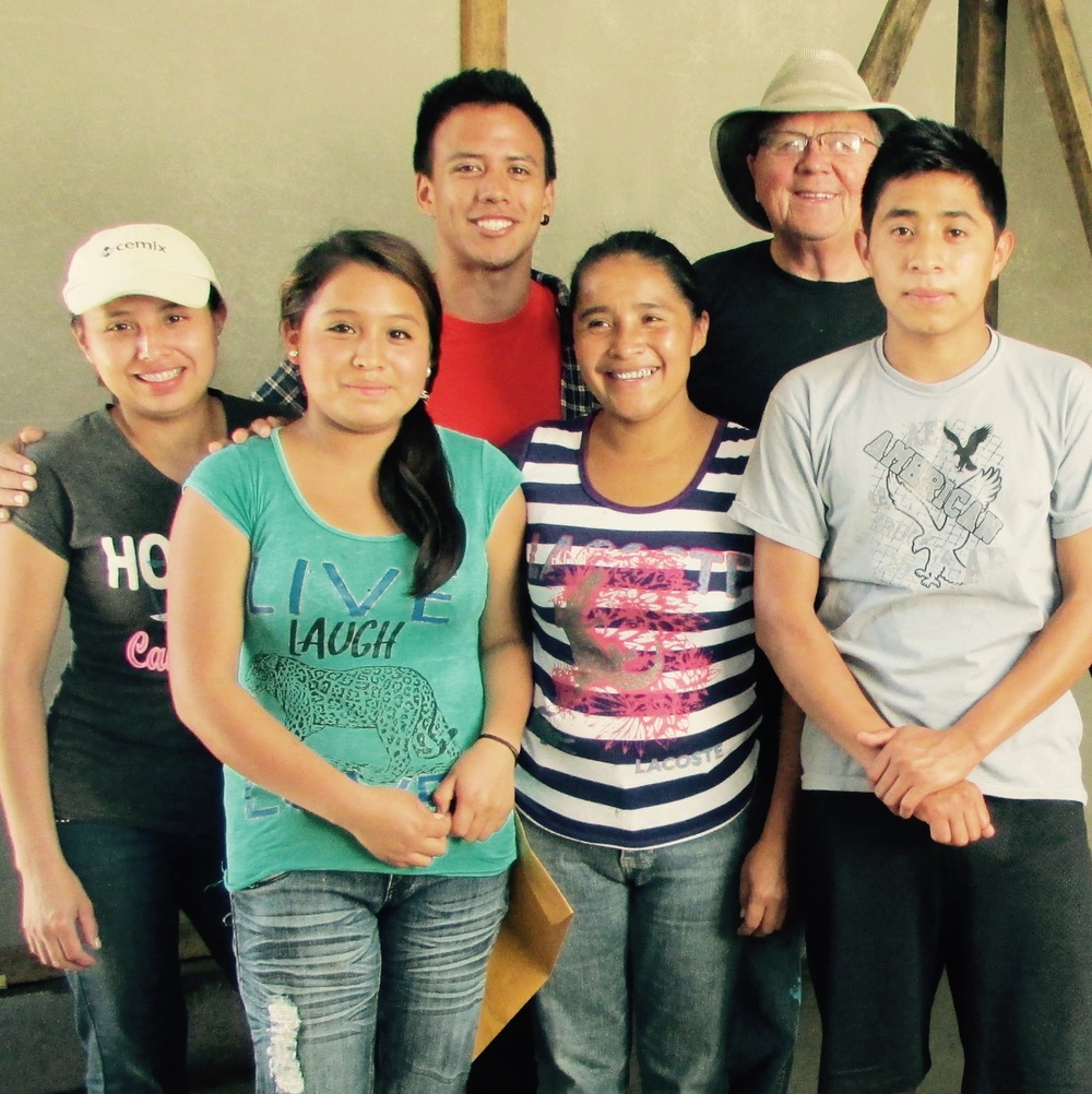 Maria inside her new home with her four children and a volunteer helper