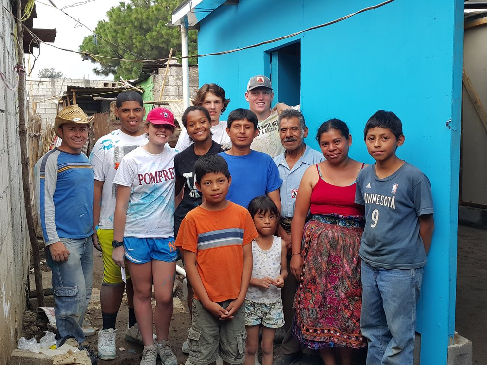 Mynor far right with family members and build volunteers in front of new home