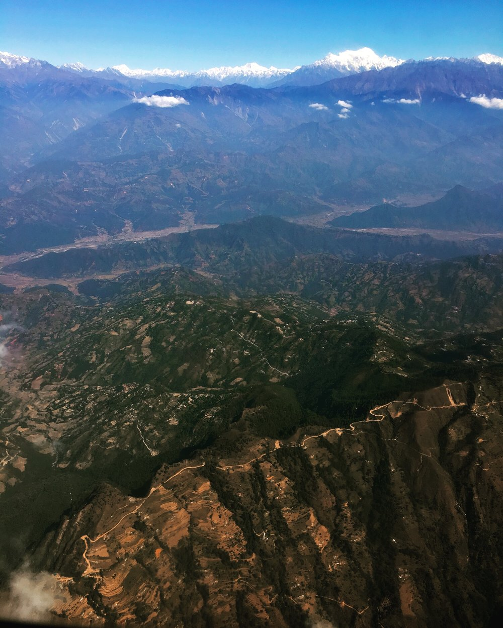 Nov 17.2, 2016   From the air Nepal remains lined by prayer flags atop small village homes and coursing down disparate rounded temple stupas. I can see the long, serpentine road that connects Kathmandu to Pokhara. Those famous gateways to the Himalaya; those places where modest dreams meet the floor and ceiling of the Earth.