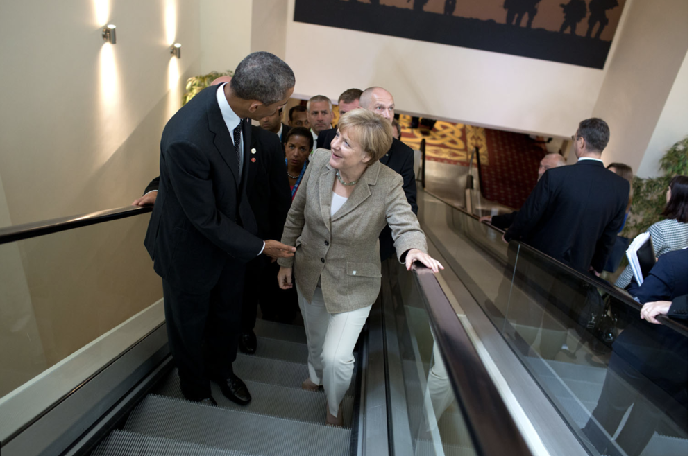 """""""President Obama in conversation with Chancellor Angela Merkel during the NATO Summit in Newport, Wales.""""    Public Domain:   Official White House Photo   by Pete Souza (04 September 2014)."""