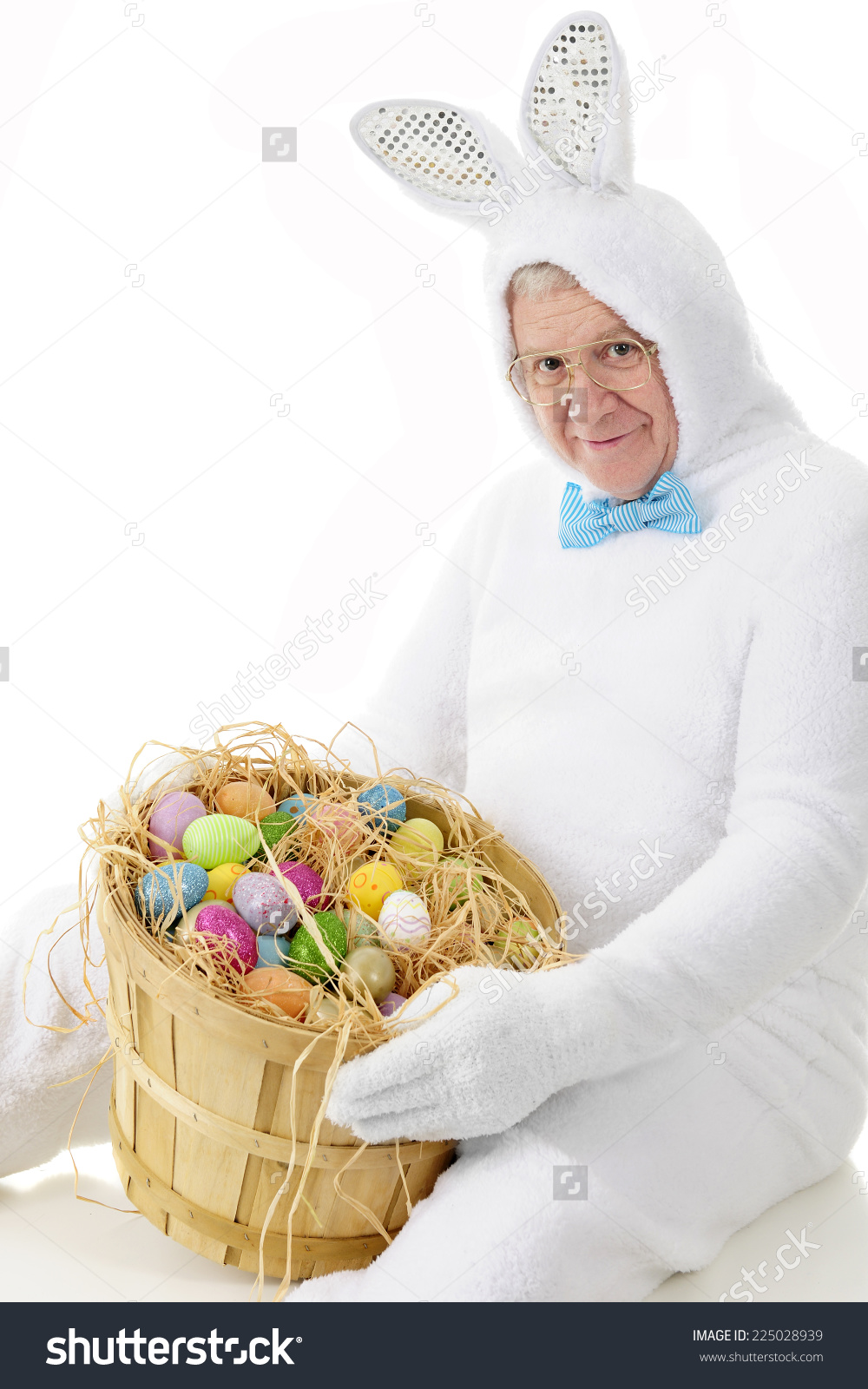Title: A senior adult man in an easter bunny outfit happily showing off a bushel of colorful eggs Grandpa, I told you to skip the outfit!