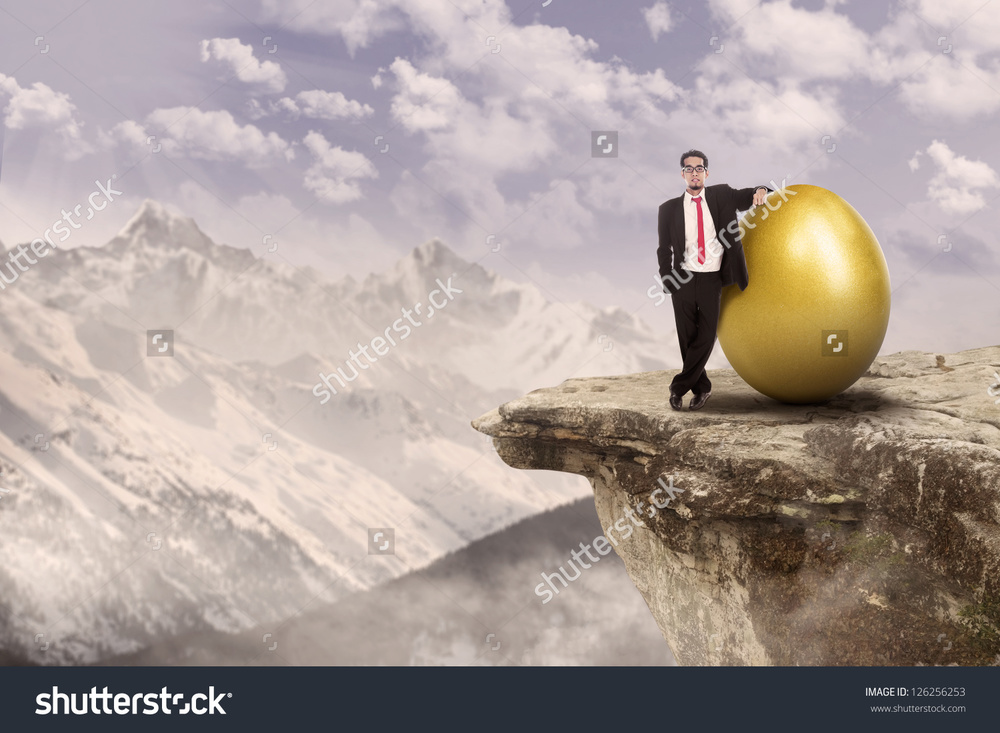 Title: Businessman standing on top of a mountain beside golden egg Seriously, tell us, when would you use this photo?