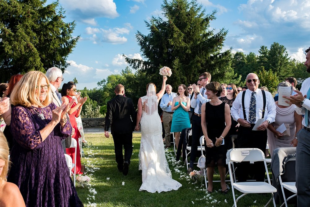 small wedding crowd cheers as bride and groom walk down the aisle