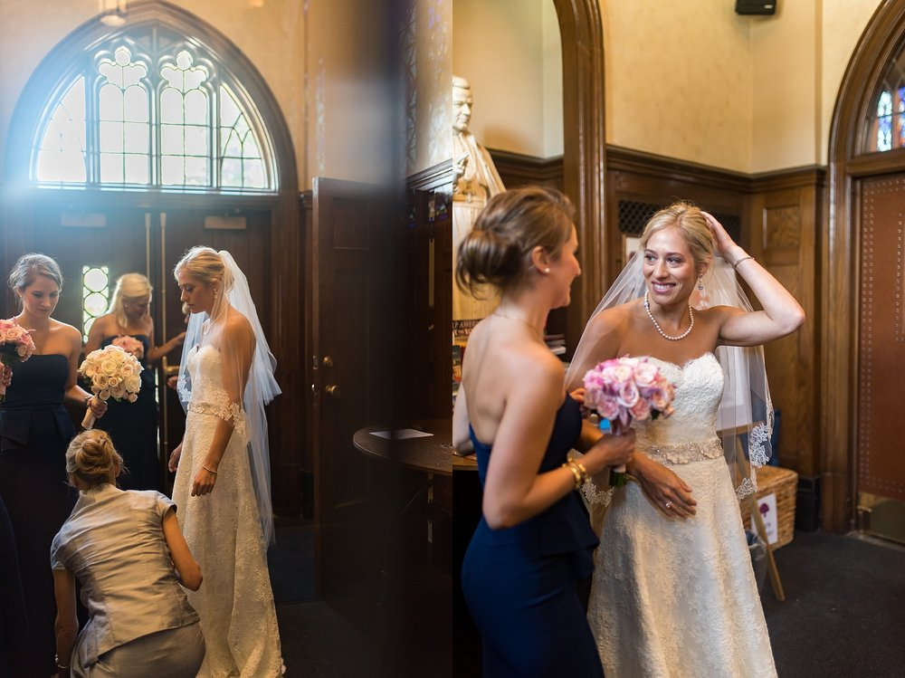 bridesmaid helping bride in longmeadow catholic church.jpg