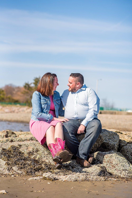couple sitting on jetty at wollaston beach