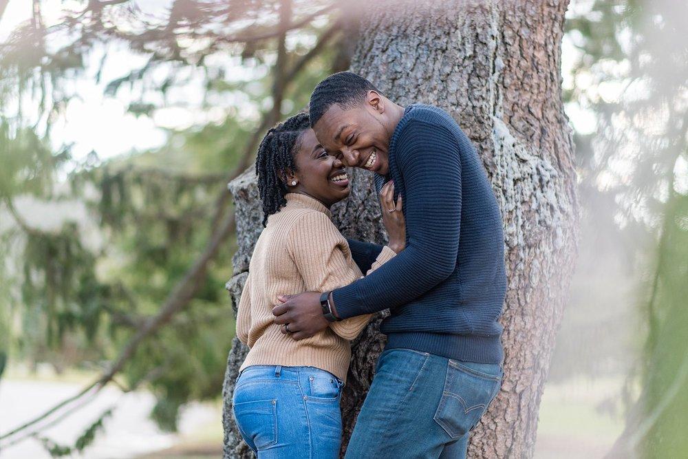 Couple laughing under tree at Arnold Arboretum