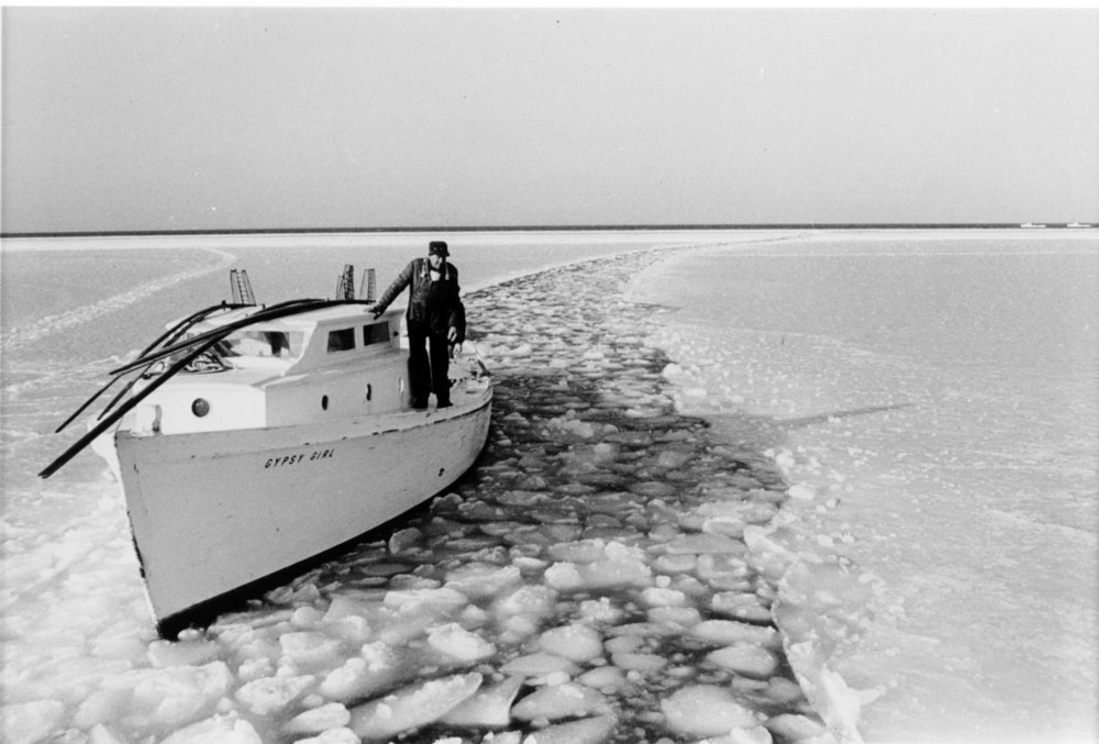 """Tonging Skiff Gypsy Girl 7,"" by Robert de Gast, collections of the Chesapeake Bay Maritime Museum.  In this 1969 image, Tilghman Island waterman Ben Gowe gingerly follows the state icebreaker back to safe harbor after a day's tonging during a cold snap. In icy winters, the state works to keep the Chesapeake's principal channels open to navigation and deploys small icebreakers to help watermen return safely to port. Photojournalist Robert de Gast rode the icebreaker while documenting the Chesapeake's oyster industry in 1969 and 1970 in preparation for a book,  The Oystermen of the Chesapeake ."