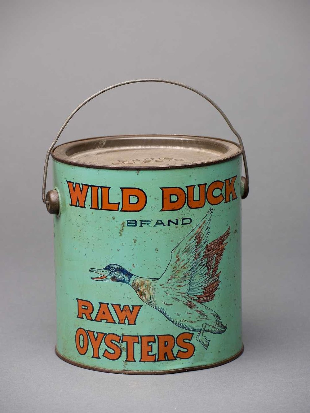 "In the late 19th century, the Chesapeake produced more oysters than any other region in the world. The oyster-packing industry was centered in Baltimore, and Roy E. Roberts was just one among scores of oyster packers in the city. To individualize their brands among such stiff competition, packers used distinctive names and imagery for their products to make them memorable to the consumer. Although Robert would later market most of his oysters under the ""Maryland Beauty"" brand, he briefly used the ""Wild Duck"" brand- making it among the rarest, most valuable, and most collectible oyster cans in the world.     R.E. Roberts, Inc., ""Wild Duck Brand Raw Oysters,"" R.E. Roberts, Inc., c. 1920. Lithograph on tinplate, 18.4 x 17.1 cm. Museum purchase, 2002.40.69. Digital image by David W. Harp © Chesapeake Bay Maritime Museum."