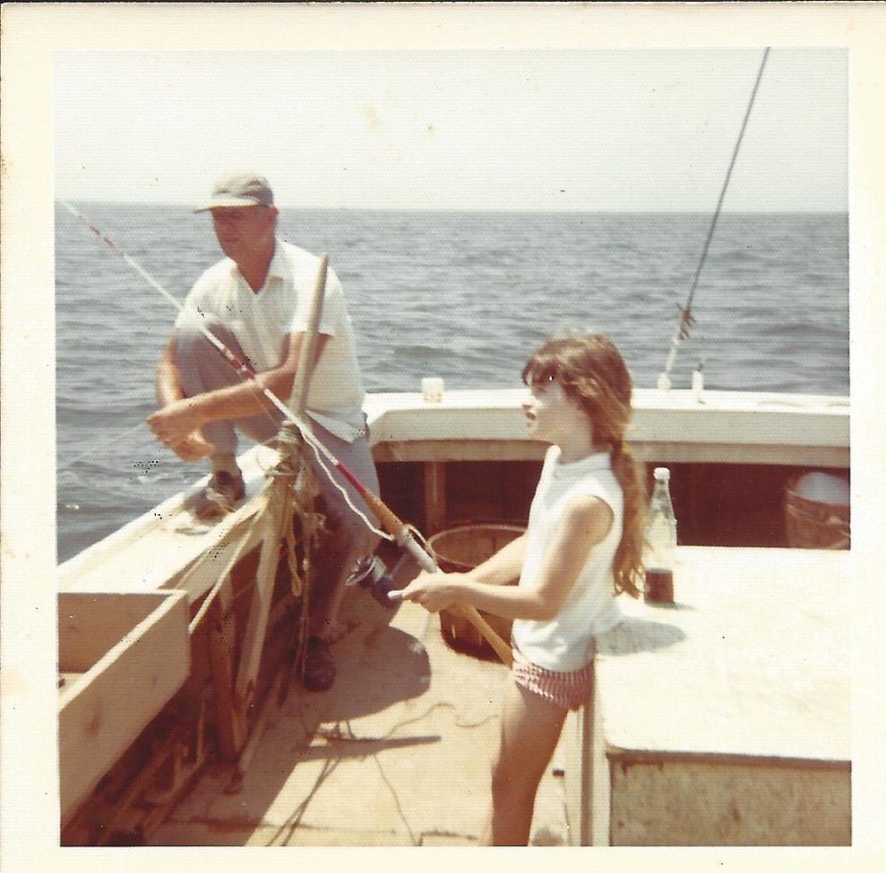 """This 1972 photo of Sherri Marsh Johns and her dad, Calvin """"Junie"""" Marsh, was submitted for CBMM's upcoming exhibit, """"Snapshots to Selfies: 50 years of Chesapeake Summers."""" This exhibit, a collection of community-submitted summer stories and photos, will feature the memories of Bay folks from the last 50 years, doing what we have always done during the Chesapeake's laziest days- enjoying the water.   Sherri writes,   """"This was my first fishing trip after Dad bough my first fishing rod. We  are aboard his 42 ft. Bay-built box stern, the Sherri Michelle.  Although he was a waterman he didn't own a fishing rod –if you look  closely you will see he is using a hand line. I can still see those  tough hands able to pull up a fishing line without using a reel.    Buying a fishing rod for me when he didn't have one himself was such a  gesture of love from a man who was not good at communicating emotions.  Here I too young to appreciate any of that and am staring with at the  rod with complete impatience waiting for a bite.    When I look at this photo and imagine what it would look like if it were  taken now. The boat would be fiber glass, the glass coke bottle would  be a cardboard juice box, I would under the protection of sunscreen,  glasses and a hat and required to wear a PFD. Many things change,  fortunately not the tradition of fathers teaching their daughters to  fish.""""     To submit your own photos and stories, go to  http://bit.ly/1c2t2bT  and share your summer snaps from the last 50 years!"""