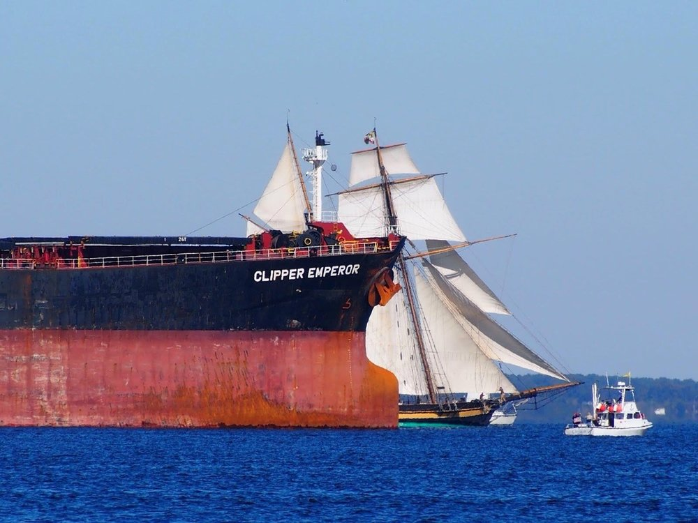 Two world collide (fortunately, not literally) as the Pride of Baltimore navigates the freighters at the start of Chesapeake Bay Schooner Race.