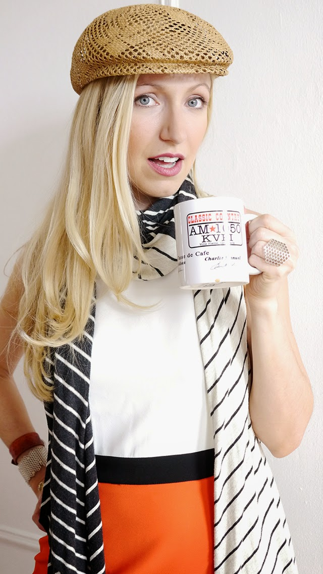 girl drinking coffee, ratan hat, blonde hair, stripe scarf