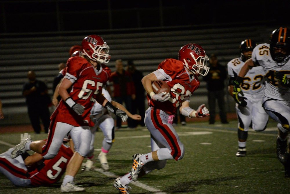 Senior Sean Saunders follows his blockers as he runs the ball down the field. (Photo by Sofia Guerra)