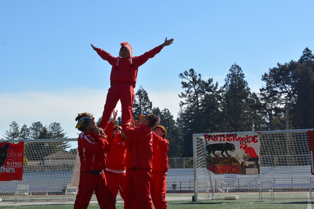 Junior Aaron Gomez is lifted by his fellow dance members at the top of a pyramid.