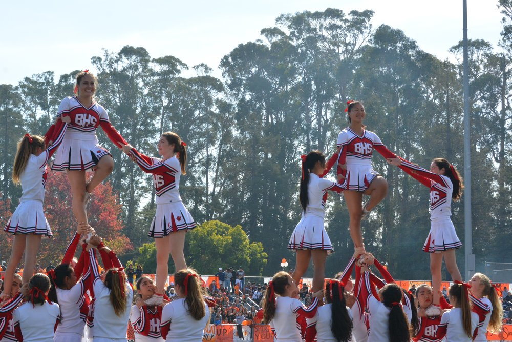 Seniors Katherine Kawaguchi and Sloan Cimmet smile on top of the squad pyramid.